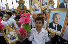 Cambodian students hold portraits of former King Norodom Sihanouk, right, King Norodom Sihamoni, and flowers during an Independence Day celebration at the Independence Monument in Phnom Penh, Cambodia, Wednesday, Nov. 9, 2011.