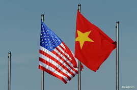 The U.S. flag (L) flutters next to the Vietnamese flag during a welcoming ceremony for U.S. Defense Secretary Ash Carter (not pictured) at the Defense Ministry in Hanoi, Vietnam June 1, 2015. Carter discussed his call for an end to island-building in
