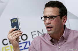 Venezuelan opposition leader and Governor of Miranda state Henrique Capriles holds a copy of the country's constitution while he talks to the media during a news conference in Caracas, Venezuela, April 25, 2016.