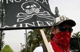 "FILE - A protester holds a sign that reads in Spanish ""No to mining"" at a protest against Canada's gold and silver mining operations in northern El Salvador, outside Canada's Consulate office in San Salvador, May 21, 2007."
