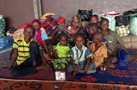 Yaman Ahmat, center, sits with her children at Bangui Airport after only hours earlier, her husband Marcus Madi, had put her and their eight children including newborn daughter Ashta onto a flight to the capital in a desperate bid to save their lives