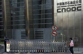 FILE - A woman walks past the entrance of the headquarters of China National Offshore Oil Corp (CNOOC) in Beijing, Sept. 23, 2010.