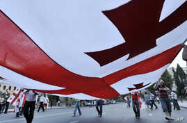 Georgians carry a giant national flag while gathering for an anti Russian demonstration in front of the Parliament building in Tbilisi, Georgia, Tuesday, Aug. 12, 2008. Russia ordered a halt to its military action in Georgia on Tuesday after five day