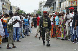Residents of the Treichville neighborhood gather outside the damaged former base of Laurent Gbagbo's Republican Guards, as soldiers loyal to Alassane Ouattara occupy it, in Abidjan, Ivory Coast, April 15, 2011