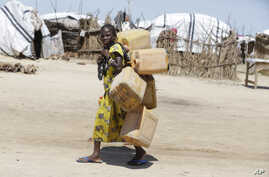 In this photo taken Sunday Aug. 28, 2016 a girl displaced by Islamist Extremists carries empty plastic containers at a camp Maiduguri, Nigeria.