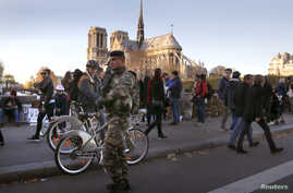 A soldier patrols on a bridge near Notre Dame cathedral following deadly attacks in Paris, Nov. 15, 2015.