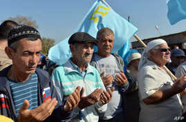 FILE - Crimean Tatars pray as they block the road at the checkpoint between Ukraine and Crimea, in Chongar, September 20, 2015.
