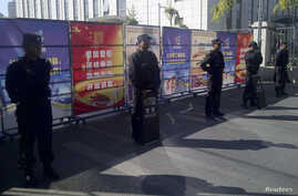Policemen in riot gear guard a checkpoint near a courthouse where ethnic Uighur academic Ilham Tohti's trial is taking place in Urumqi, Xinjiang Uighur Autonomous Region, Sept. 17, 2014.