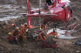 Firefighters prepare a body to be lifted away by a helicopter, after pulling the dead person from the mud days after a dam collapse in Brumadinho, Brazil, Jan. 28, 2019.