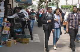 Young Egyptians pass by a kiosk near Ain Shams University in Cairo, April 21, 2016. College students in Egypt worry about jobs, as the country has long had more college graduates than jobs in desired professions. (H. Elrasam/VOA)