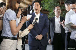 Japan's Prime Minister Shinzo Abe (C) speaks to media at his official residence in Tokyo, July 3, 2014.