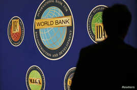 A man is silhouetted against the logo of the World Bank at the main venue for the International Monetary Fund (IMF) and World Bank annual meeting in Tokyo, October 10, 2012.