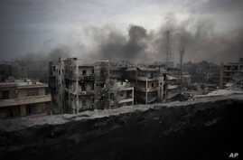 FILE - Smoke rises over Saif Al Dawla district, in Aleppo, Syria, Oct. 2, 2012.