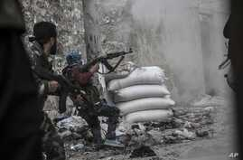 A rebel fighter retreats for cover as enemy fire targets the rebel position during clashes at the Moaskar front line, one of the battlefields in the Karmal Jabl neighborhood, of Aleppo, Syria, October 24, 2012.