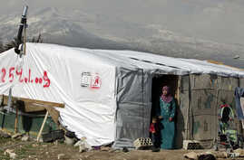 FILE - A Syrian refugee stands outside her tent in a Syrian refugee camp in the eastern town of Houch al-Harimeh, Lebanon.