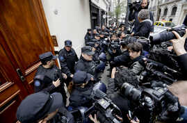 Police keep the press at bay as they execute a search warrant at the home of Senator and Former President Cristina Fernandez, in Buenos Aires, Argentina, Aug. 23, 2018.