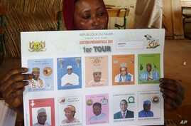 A woman holds a ballot paper bearing portraits of the presidential candidates at a polling station, in Niamey, January 31, 2011.