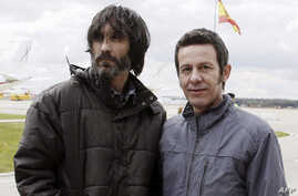 El Mundo correspondent Javier Espinosa (R) and freelance photographer Ricardo Garcia Vilanova arrive at the military airbase in Torrejon de Ardoz, near Madrid, March 30, 2014.