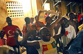 Supporters of Guinean presidential candidate Alpha Conde celebrate at his headquarters after it was announced by the National Independent Electoral Commission that the preliminary results showed he had won Guinea's tense presidential election, 15 Nov