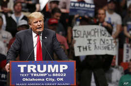 """FILE - Republican presidential candidate Donald Trump speaks at a rally as a man holds up a sign that reads """"Islamophobia is not the answer"""" in Oklahoma City, Feb. 26, 2016."""