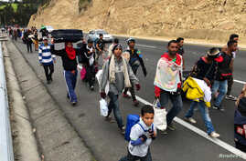 Venezuelan migrants walk along the Ecuadorean highway to Peru before new rules requiring they hold a valid passport kick in, at Tulcan, Ecuador, Aug. 21, 2018.