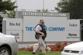 ATF police officer with a sniffing dog walks out the industrial complex in Harford County, Maryland, Sept. 20, 2018.