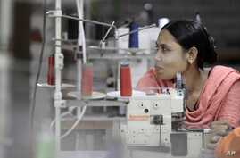 FILE - Bangladeshi garment worker Asma, who worked on the 4th floor of Rana Plaza garment factory that collapsed exactly a year ago, works at a factory meant to rehabilitate survivors of the accident, the worst in the history of the garment industry,