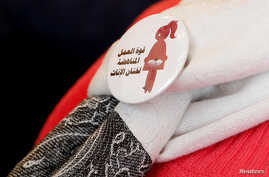 """A badge reads """"The power of labor against FGM"""" is seen on a volunteer during a conference on International Day of Zero Tolerance for Female Genital Mutilation (FGM) in Cairo, Egypt, Feb. 6, 2018."""