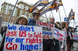 FILE - Protesters holding anti-American signs are seen gathered in front of the U.S. Embassy at a rally against what they see as American mingling in Russia's internal affairs, in Moscow, Russia, March 7, 2015.