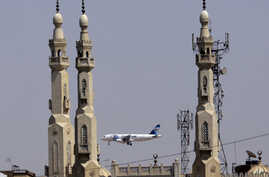 ILE - In this May 21, 2016, file photo, an EgyptAir plane flies past minarets of a mosque as it approaches Cairo International Airport, in Cairo, Egypt.