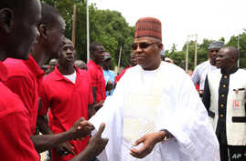 "FILE- In this Thursday, Aug. 8, 2013 file photo, Borno state governor Kashim Shettima, right, shake hands with members of the ""Civilian JTF"",  in Maiduguri Nigeria.  The governor of Nigeria's northeast Borno state Shettima has temporarily relocated t"