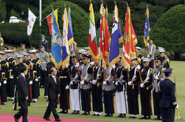 Burma's President Thein Sein, second from left, inspects an honor guard with his South Korean counterpart Lee Myung-bak, left, during a welcome ceremony at the presidential Blue House in Seoul, South Korea, October 9, 2012.