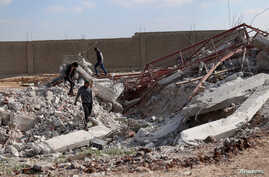 Youth inspect rubble of a damaged house after an airstrike yesterday on rebel-held Daraa al-Balad, Syria, April 7, 2017.