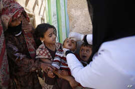 FILE - A boy receives a polio vaccination during a house-to-house polio immunization campaign in Sanaa, Yemen.