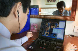 "FILE - Tran Huynh Duy Thuc, founder of a Vietnamese Internet provider, makes a telephone call via the Internet in his office in Hanoi, July 3, 2003.Ho Chi Minh City is quickly becoming a destination for ""tech nomads"" – online entrepreneurs looking to"