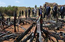 French President Francois Hollande, third right, and his Defense Minister Jean-Yves Le Drian, second right, inspect arms confiscated from ex-Seleka rebels and Anti-balaka militia by the French military of operation Sangaris, and displayed at a French