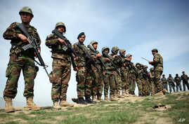 FILE - Afghan National Army soldiers stand guard following weeks of heavy clashes to recapture the area from Taliban militants in Dahna-e-Ghori district, Baghlan province, Afghanistan, Mar. 15, 2016. But Taliban fighters retook the district in early
