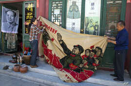 """Vendors unfurl a banner from 1969 depicting former Chinese leader Mao Zedong as he """"inspects the great army of the Cultural Revolution"""" and the slogan """"Navigating the seas depends on the helmsman"""" at a curio market in Beijing, China, May 16, 2016."""