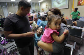 Honduras immigrants seeking asylum, Carlos Fuentes Maldonado, left, stands with his wife, Jennifer Maradiaga, and daughters Mia, 1, and Britany, 4, after they were reunited, July 23, 2018, in San Antonio, Texas.