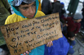 A migrant boy shows a banner saying he wants to travel to Germany rather than camps set up by Turkey, during a protest demanding the opening of the border between Greece and Macedonia in the northern Greek border station of Idomeni, Greece,  March 23...