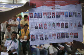 People watch as electoral officials show ballot papers during vote counting at a polling station in Jakarta, April 9, 2014.