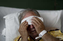 FILE - A flu patient places a cold compress on his forehead at Upson Regional Medical Center in Thomaston, Ga., Feb. 9, 2018.