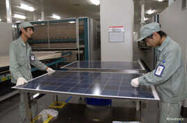 FILE - Employees work on a solar panel production line at Suntech Power Holdings headquarters in Wuxi, Jiangsu.
