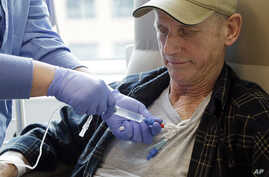 FILE - A lymphoma patient receives cellular immunotherapy as part of a study at the Fred Hutchinson Cancer Research Center in Seattle, Washington, March 21, 2017.