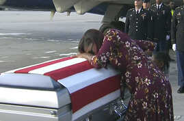 In this frame from video, Myeshia Johnson cries over the casket in Miami, Florida, Oct. 17, 2017, of her husband, Sgt. La David Johnson, who was killed in an ambush in Niger.