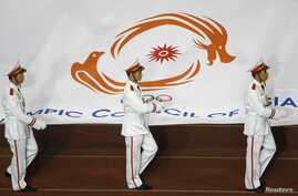 FILE - Soldiers carry the flag of the Olympic Council of Asia during an opening ceremony.