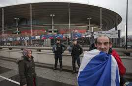 A French supporter wrapped in his national flag passes by police officers guarding the Stade de France stadium prior to the international exhibition soccer match between France and Russia in Saint Denis, north of Paris, March 29, 2016.