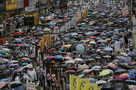People under umbrellas fill in a street during a march at an annual protest in downtown Hong Kong Tuesday, July 1, 2014. Hong Kong residents marched through the streets of the former British colony to push for greater democracy in a rally fueled by a