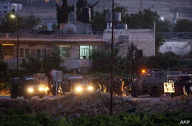 Israeli soldiers stand next to their vehicles in the village of Halhul, near the West Bank town of Hebron, where the bodies of the three missing Israeli teenagers were found, June 30, 2014.