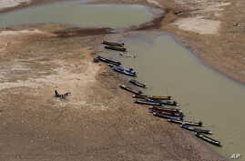 FILE - Fishing boats park downstream from Lamtakong dam during a recent period of extreme drought in Nakhon Ratchasima, Thailand. Thailand's rainy season officially began in the last week of May, but it rained only once in the Ban Lueam district in n